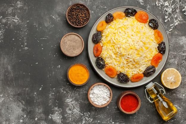 Bovenaanzicht rijstkommen met kruiden bord rijst met gedroogde vruchten citroen fles olie
