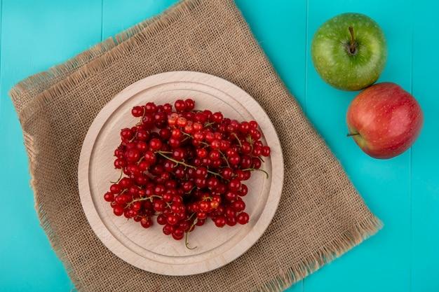 Bovenaanzicht rode aalbes op een bord met appels op een lichtblauwe achtergrond