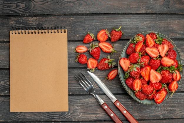 Bovenaanzicht rode aardbeien gesneden en hele vruchten op donker houten rustiek bureau