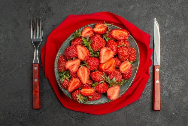Bovenaanzicht rode aardbeien in plaat op donkere achtergrond