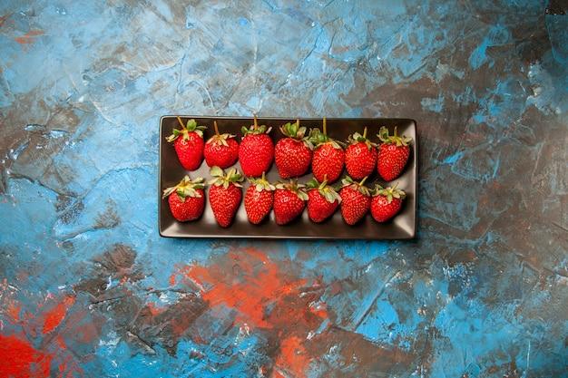 Bovenaanzicht rode aardbeien in zwarte pan op blauwe achtergrond