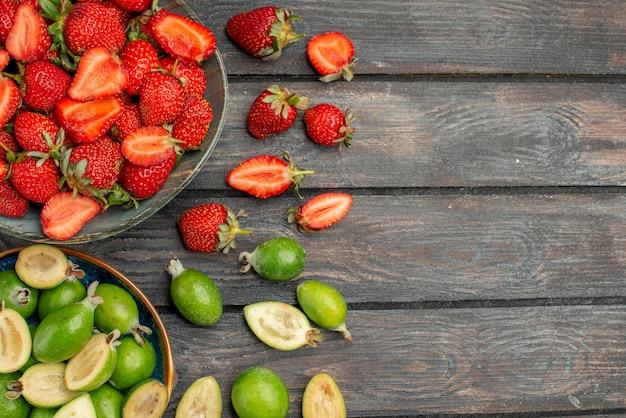Bovenaanzicht rode aardbeien met verse feijoa's op donker houten rustiek bureau