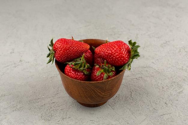 Bovenaanzicht rode aardbeien verse zachte sappige binnenkant bruine pot op de grijze achtergrond