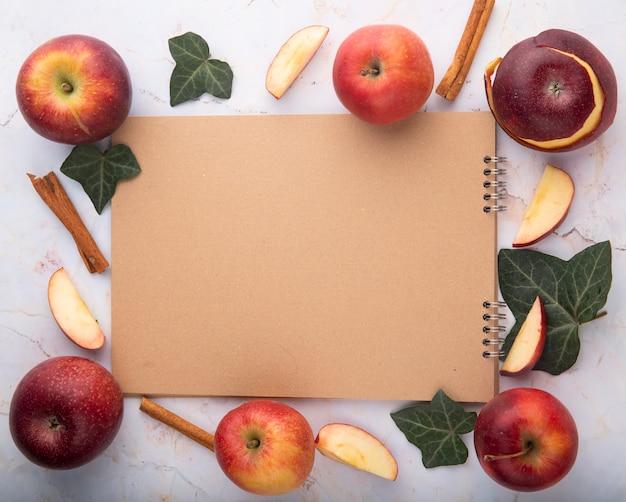 Bovenaanzicht rode appels met kaneel klimop bladeren en kopie ruimte op witte achtergrond