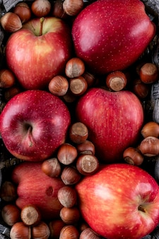 Bovenaanzicht rode appels met noten in mand textuur verticaal