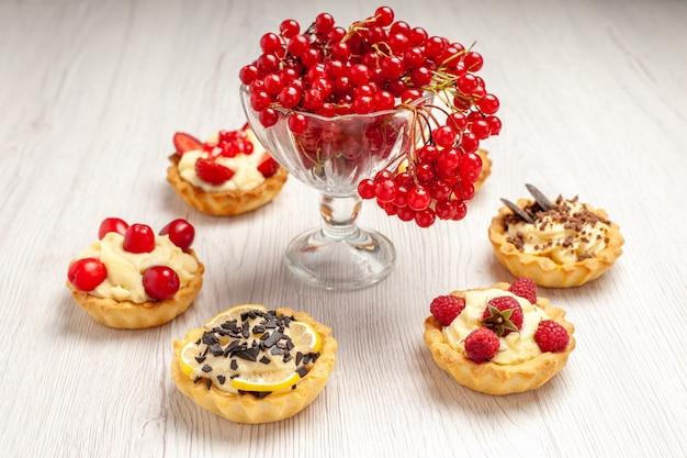 Bovenaanzicht rode bessen in een kristalglas op het rode ovale kanten kleedje en taartjes op de witte houten tafel