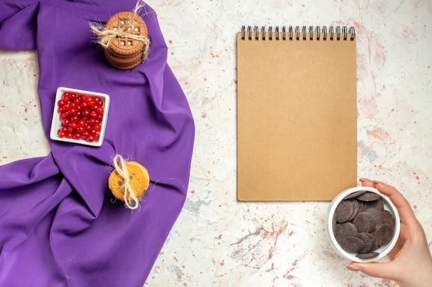 Bovenaanzicht rode bessen in komkoekjes vastgebonden met touw op paarse sjaal kladblok chocoladekom in vrouwenhand op witte tafel