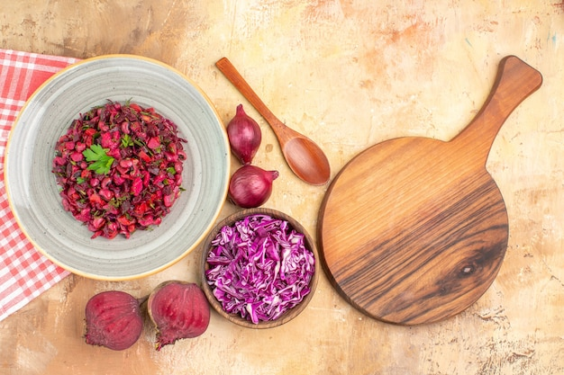 Bovenaanzicht rode bietensalade gekleed met peterseliebladeren op basis van rode bieten, rode uien en kom gehakte kool op een houten ondergrond met ruimte voor tekst
