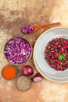 Bovenaanzicht rode bietensalade op basis van rode uien, gehakte kool, kurkuma en gemalen peper in een grijze keramische plaat op een houten ondergrond met kopieerruimte