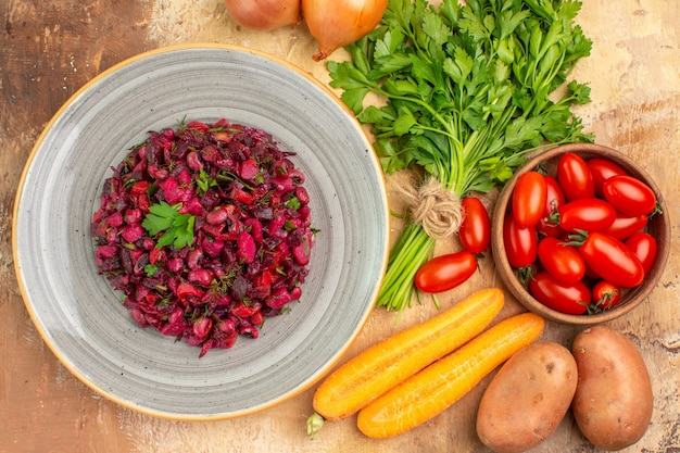 Bovenaanzicht rode bietensalade op een keramische plaat en ingrediënten voor de bereiding ervan op een houten ondergrond