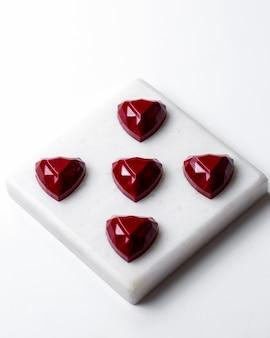Bovenaanzicht rode chocolade hartvormige snoepjes op witte stand
