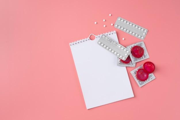 Bovenaanzicht rode condooms en pillen arrangement