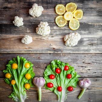 Bovenaanzicht rode en gele tomaten met sla, bloemkool, citroenen, knoflook op donkere houten achtergrond.