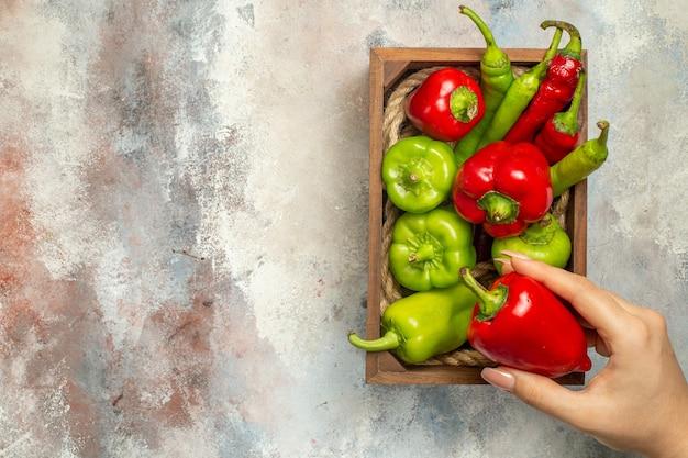 Bovenaanzicht rode en groene paprika hete pepers in houten doos paprika in vrouw hand op naakt oppervlak kopie plaats