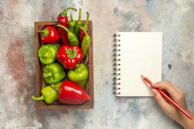 Bovenaanzicht rode en groene paprika hete pepers in houten kist een notebook potlood in vrouw hand op naakt oppervlak