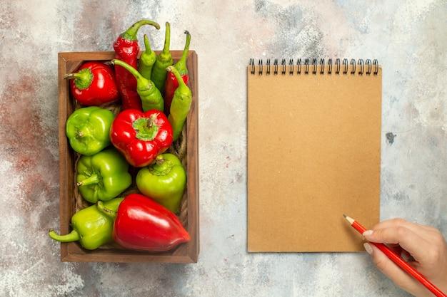 Bovenaanzicht rode en groene paprika hete pepers in houten kist notebook rood potlood in vrouwelijke hand op naakt oppervlak