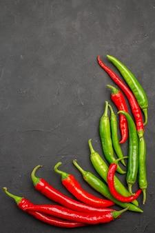 Bovenaanzicht rode en groene paprika's aan de rechterkant van zwarte tafel met vrije ruimte