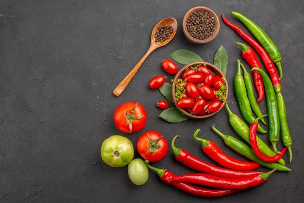 Bovenaanzicht rode en groene paprika's en een kom met cherrytomaatjes, zwarte peper en rode en groene tomaten aan de rechterkant van het zwarte oppervlak