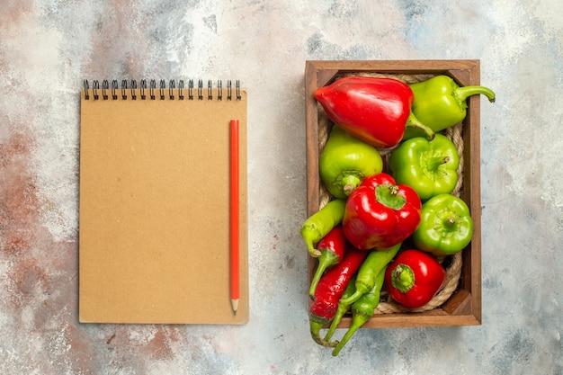 Bovenaanzicht rode en groene paprika's hete pepers in houten doos notebook rood potlood op naakt oppervlak