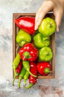 Bovenaanzicht rode en groene paprika's hete pepers in houten doos paprika in vrouw hand op naakt oppervlak