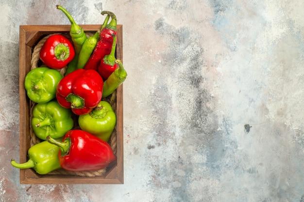 Bovenaanzicht rode en groene paprika's hete pepers in houten kist op naakt oppervlak vrije plaats