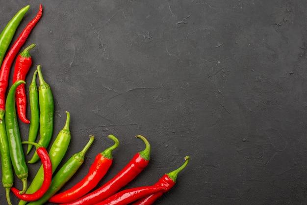 Bovenaanzicht rode en groene paprika's linksonder aan de zwarte tafel met vrije ruimte