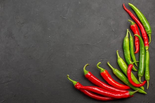 Bovenaanzicht rode en groene paprika's rechtsonder aan zwarte tafel met vrije ruimte