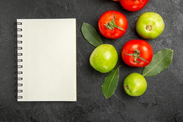 Bovenaanzicht rode en groene tomaten laurierblaadjes en een notitieboekje op donkere ondergrond