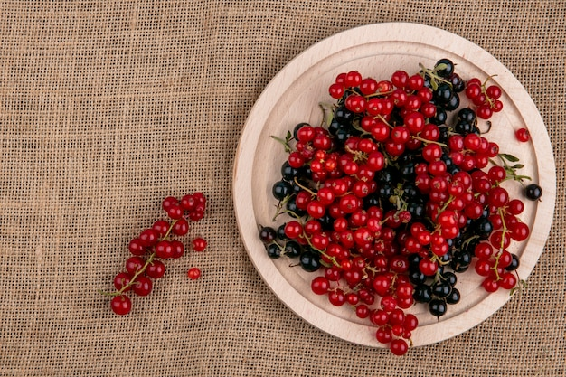Bovenaanzicht rode en zwarte bessen op een bord op een beige servet