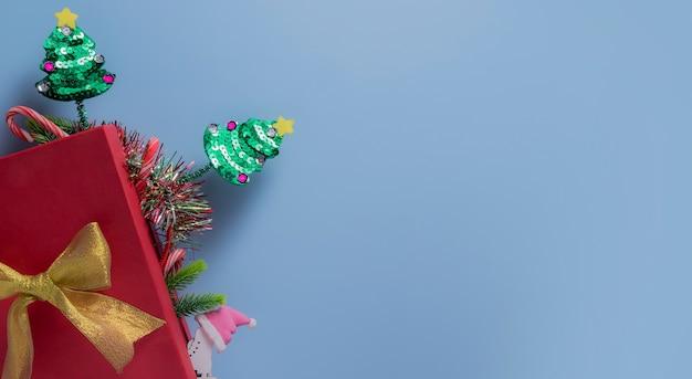 Bovenaanzicht rode geschenkdoos met kerstbomen op blauw