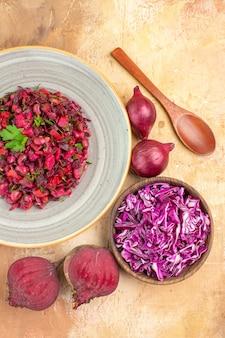 Bovenaanzicht rode gezonde salade op een bord met peterselie bladeren bovenop met twee rode uien bieten en kom gehakte kool op een houten achtergrond