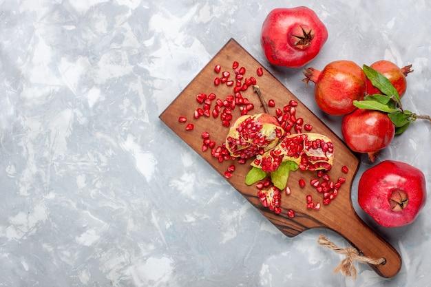 Bovenaanzicht rode granaatappel vers en sappig fruit op wit bureau