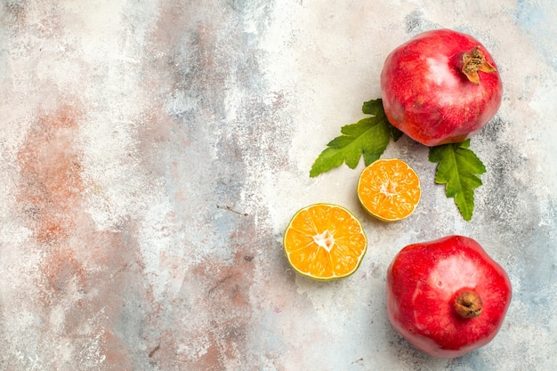 Bovenaanzicht rode granaatappels citroenplakken op naakt oppervlak met vrije ruimte