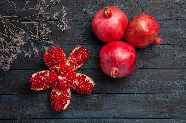 Bovenaanzicht rode granaatappels gepilde granaatappel naast boomtakken en drie granaatappels op donkere ondergrond
