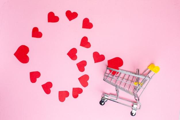 Bovenaanzicht rode harten die een grote hartvormige mini-trolley op blauwe tafel vormen