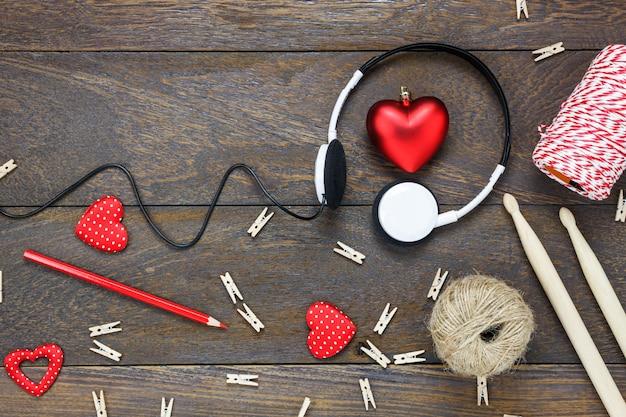 Bovenaanzicht rode hartvorm luisteren muziek door koptelefoon met decoraties dun stok, potlood, touw op houten achtergrond en kopieer ruimte.
