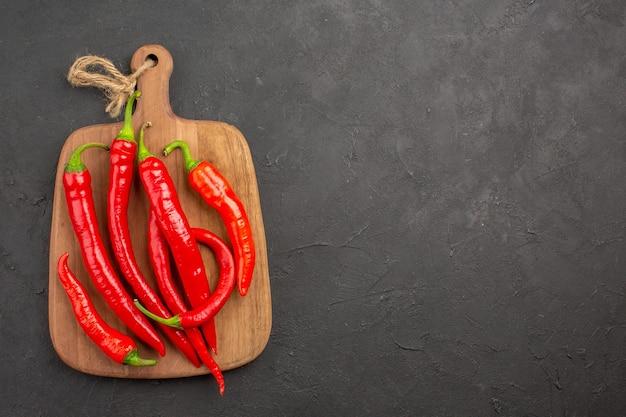 Bovenaanzicht rode hete pepers op een snijplank aan de linkerkant van de zwarte tafel met kopie ruimte