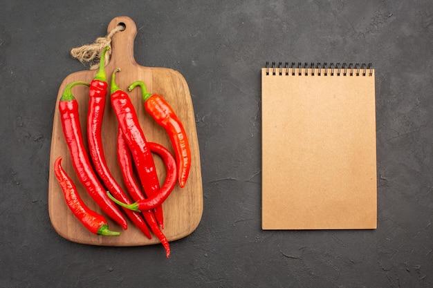 Bovenaanzicht rode hete pepers op een snijplank en een notitieblok op de zwarte tafel met kopie ruimte
