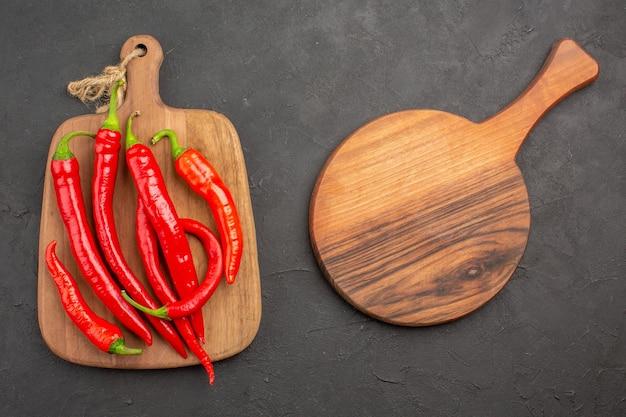 Bovenaanzicht rode hete pepers op een snijplank en een ovale snijplank op de zwarte tafel met kopie ruimte