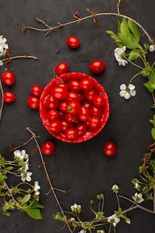 Bovenaanzicht rode kerstomaten rond witte bloemen op de grijze vloer