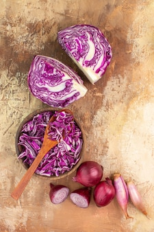 Bovenaanzicht rode kool en uien voor zelfgemaakte salade op een houten ondergrond met kopieerruimte