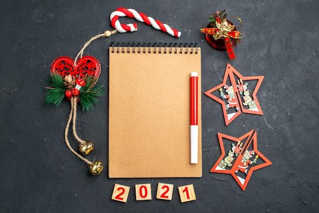 Bovenaanzicht rode markering op notebook staande in een cirkel van verschillende kerstversieringen op donkere geïsoleerde oppervlakte nieuwjaarsfoto