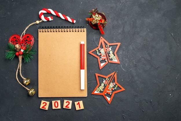 Bovenaanzicht rode markering op notebook staande in een cirkel van verschillende kerstversieringen op donkere geïsoleerde oppervlakte vrije ruimte