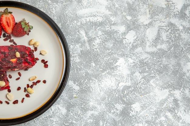Bovenaanzicht rode nougat gesneden met noten en verse rode aardbeien op wit bureau