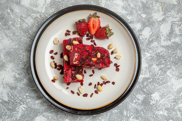 Bovenaanzicht rode nougat gesneden met noten en verse rode aardbeien op witte ondergrond