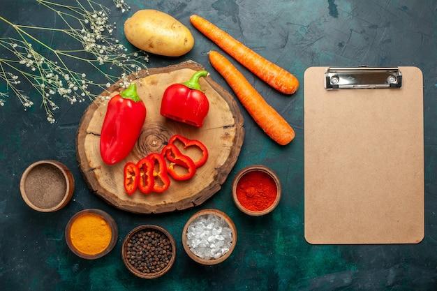 Bovenaanzicht rode paprika met verschillende kruiden op donkergroen oppervlak plantaardig pittig warm eten