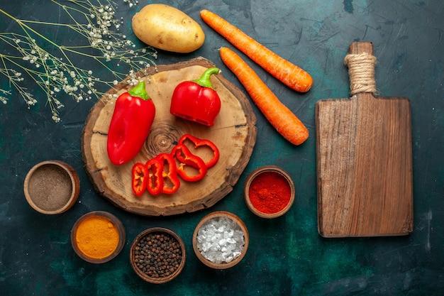 Bovenaanzicht rode paprika met verschillende kruiden op donkergroene groenten pittig warm eten