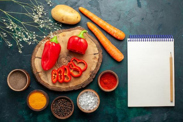 Bovenaanzicht rode paprika met verschillende smaakmakers op donkergroen bureau groente pittig warm eten