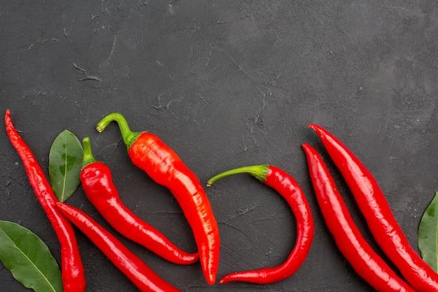 Bovenaanzicht rode paprika's en bladeren op zwarte tafel met kopie ruimte