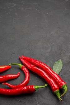 Bovenaanzicht rode paprika's en loofblaadjes aan de onderkant van zwarte ondergrond
